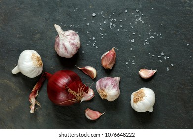 Arrangement of garlic and onions with rock salt on a natural slate table with copy space