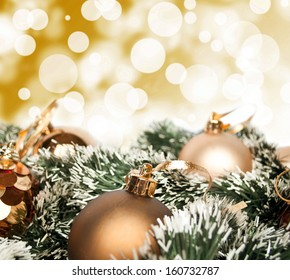 An arrangement of golden Christmas baubles against a festive bokeh of twinkling gold lights with copyspace