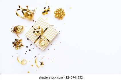 An arrangement of golden Christmas decorations and gift boxes on white background. Flatlay. Copy space