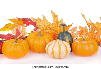 Arrangement of gourds with autumn leaves on a white surface and background