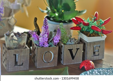 Arrangement of lavender flowers, peppers and suculents artificial decorating box and forming the word love