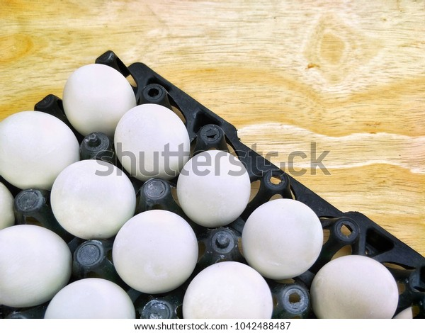 The arrangement of many salted eggs in plastic egg pan on wooden floor table background in food preservation concept