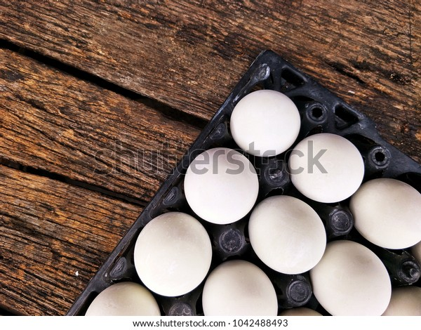 The arrangement of many salted eggs in plastic egg pan on the old wooden table floor background in food preservation concept