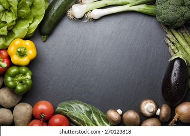 Arrangement of mixed colorful vegetables, isolated on dark gray slate stone background with empty copy space.