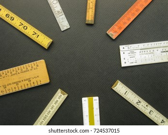 An arrangement of old vintage rulers, scales and measuring tools suggests concepts of measurement, metrics, precision, accuracy and results.
