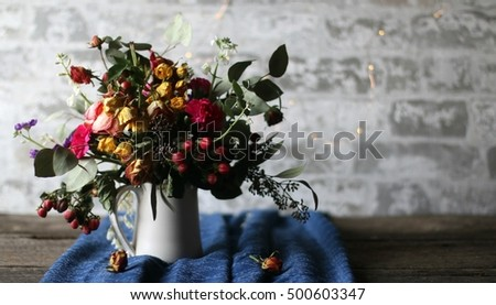Arrangement Of Partially Dried Flowers Including Yellow And Pink Roses, White Blossoms, Red Berries, Green Leaves, In Ceramic Vase With Handle With Blue Table Runner, Fairy Lights & Stone Background