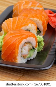 Arrangement of Philadelphia Rolls with Marinated Ginger and Wasabi on Black Plate closeup on Straw mat background