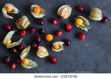 Arrangement of physalis fruit, Cape Gooseberries and cranberries, on natural slate background  with copy space