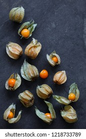 Arrangement of physalis fruit, Cape Gooseberries, on natural slate background - portrait mode with copy space top right