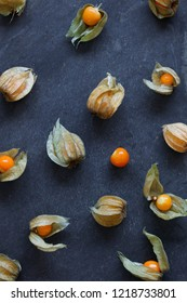 Arrangement of physalis fruit, Cape Gooseberries, on natural slate background - portrait
