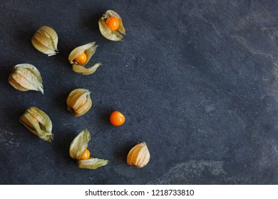 Arrangement of physalis fruit, Cape Gooseberries, on natural slate background with copy space to right