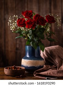 Arrangement of red roses in a vase on a wooden table and background