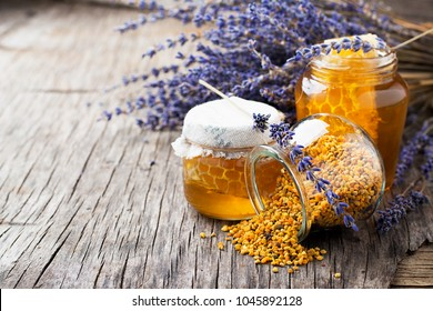 Arrangement of small glass jars with lavender honey, honeycombs and bee pollen with a bunch of dried lavender on dark wooden background. selective Focus.