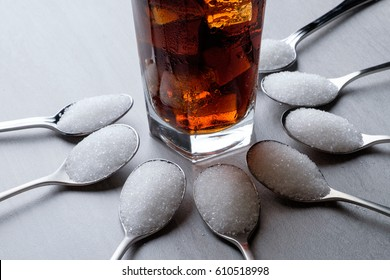 Arrangement spoons of sugar and cola / carbonated drink. Health concept on high sugar consumption.