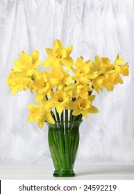 Arrangement of spring daffodils on the window cill with net curtains in the  background