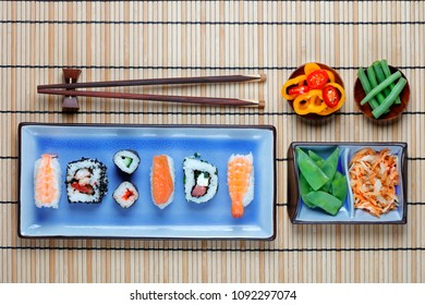 Arrangement of sushi with chopsticks, pickled vegetables and peppers