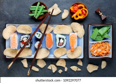 Arrangement of sushi with chopsticks, pickled vegetables and peppers on slate background