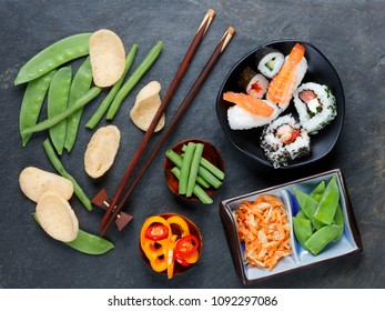 Arrangement of sushi with chopsticks, pickled vegetables and peppers with shrimp crackers on slate background