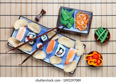 Arrangement of sushi with chopsticks, pickled vegetables and peppers with shrimp crackers