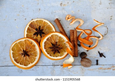 An arrangement of three dried orange slices, orange curls, cinnamon stick, nutmegs, star anise, and cloves on shabby white wood background