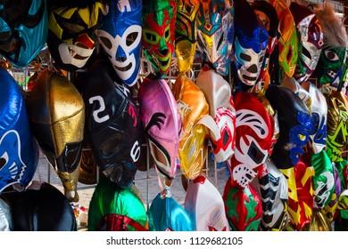 Arrangement of various luchador masks as a background.