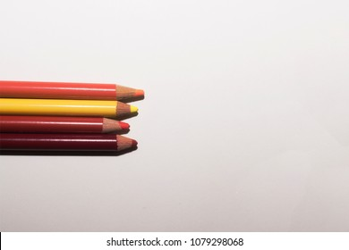 An arrangement of warm colored pencils on a paper white background
