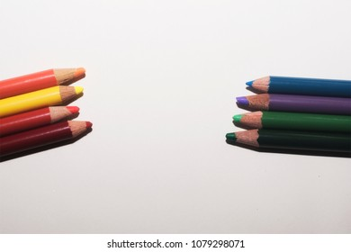 An arrangement of warm and cool colored pencils on a paper white background