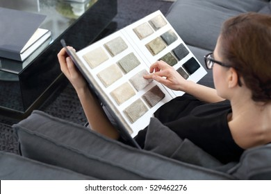 Arranging home shopping coverings. Woman chooses carpet for the living room