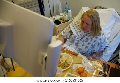 Arras, Hauts-de-France/France-March 10 2019: A female eating lunch in her hospital bed following implant surgery to help repair a broken ankle