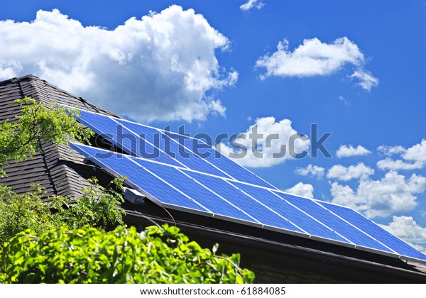 Array of alternative energy photovoltaic solar panels on roof of residential house