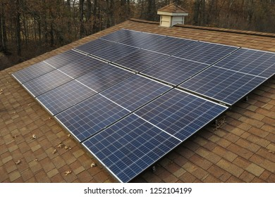 An array of black photovoltaic, solar panels collecting energy from the sun in autumn on the roof of a house.