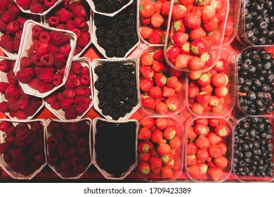 Array of bowls or shells of juicy raspberries, blackberries, strawberries and blueberries on a local street market in stockholm