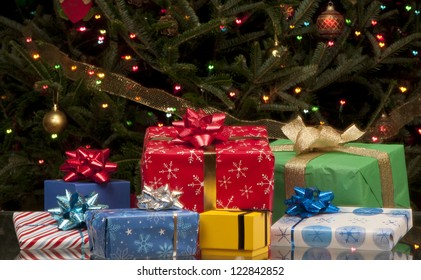 Array of Christmas presents in front of tree