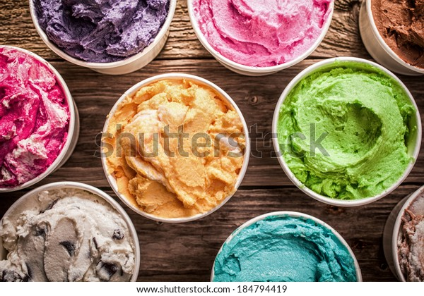 Array of different flavored colorful ice cream in plastic tubs displayed on an old wooden table at an ice cream parlor for delicious frozen snacks on a hot summer day