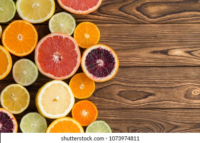 Array of fresh juicy halved citrus fruits arranged to the side on a wooden background with copy space viewed from overhead