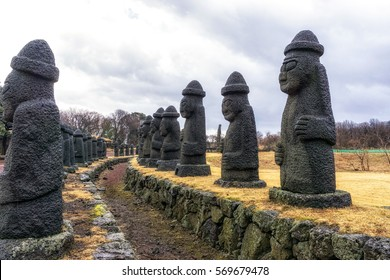 array of grandfather stones in jeju stone park, south korea
