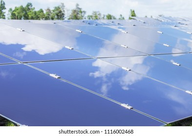 array of  solar panels or amorphous silicon solar cells or photovoltaics in solar power plant turn up skyward absorb the sunlight from the sun with blue sky and white cloud  reflection