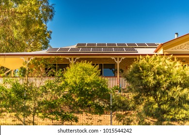 Array of solar panels on north facing roof of suburban house in sunny Queensland, installed to convert energy from sunlight to electricity, help reduce power bills and produce green energy. Copy space