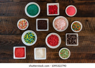 Array of Sprinkles in White Bowls Over Wooden backdrop