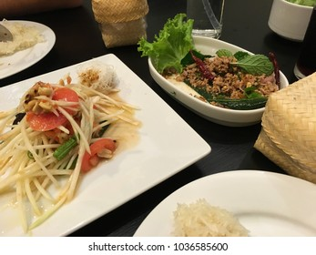 Array of Thai dishes on a black table featuring som tum (green papaya salad) and minced pork liver, on a black table with white plates and little steamer baskets of rice.