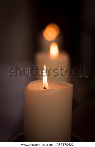 array of white candles burning in a catholic church