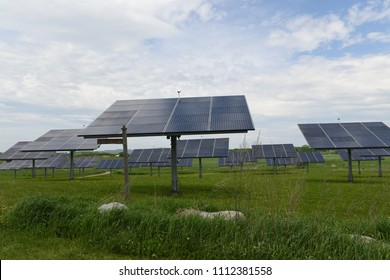 Arrays of solar panels fill a meadow under a blue and cloudy sky