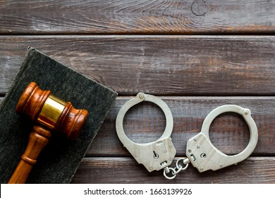 Arrest concept. Handcuffs near judge gavel on dark wooden background top-down copy space