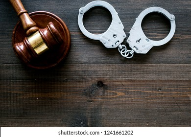 Arrest concept. Metal handcuffs near judge gavel on dark wooden background top view copy space