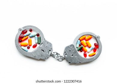 Arrest for illegal purchase, possession and sale drugs concept. Drugs as pills near handcuff on white background top view copy space