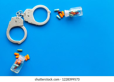 Arrest for illegal purchase, possession and sale drugs concept. Drugs as pills near handcuff on blue background top view copy space