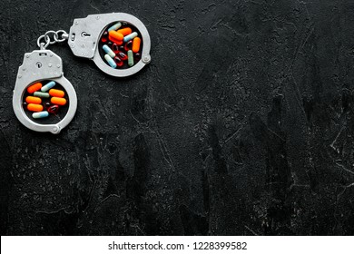 Arrest for illegal purchase, possession and sale drugs concept. Drugs as pills near handcuff on black background top view space for text