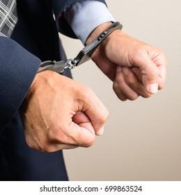 arrested businessman in handcuffs. Businessman bribetaker or briber. Concept of fraud, detention, crime and bribery