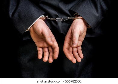 Arrested businessman in handcuffs with hands behind back - isolated on black background