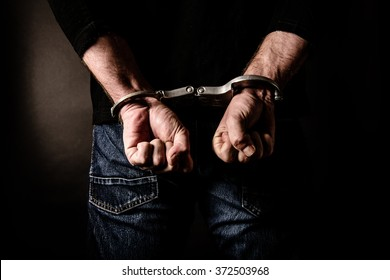 Arrested criminal with handcuffs behind his body concept for crime does not pay